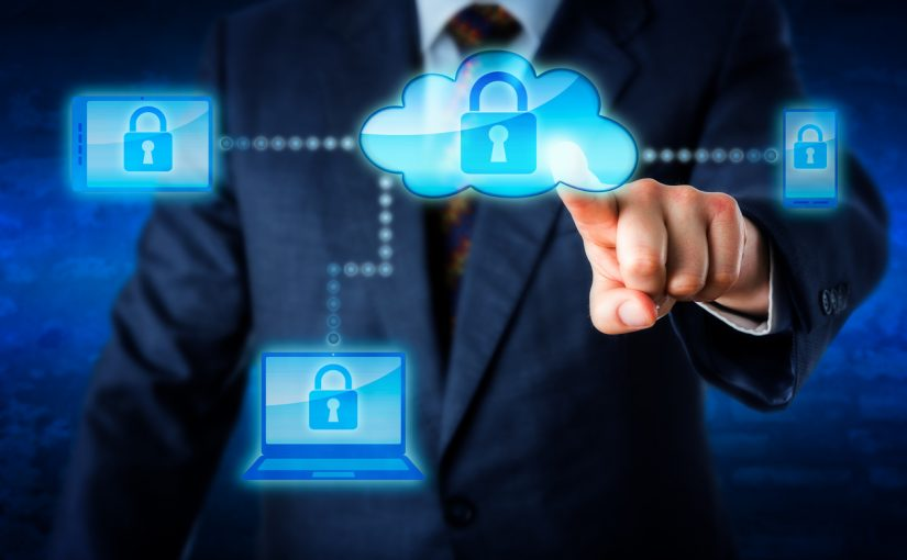 Torso of a business man in blue suit reaching forward to touch a cloud icon with index finger and lock mobile devices. Smart phone, laptop and tablet PC are in the cloud network. Technology metaphor.