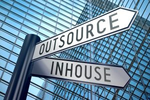 Crossroads sign with two arrows, office building - inhouse, outsource